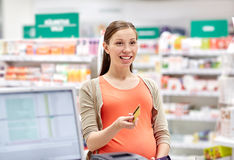 Pregnant woman with credit card in drugstore Royalty Free Stock Photography