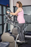 Pregnant woman on crosstrainer Royalty Free Stock Photography