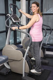 Pregnant woman on crosstrainer Stock Image