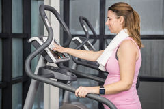 Pregnant woman on crosstrainer Royalty Free Stock Photos