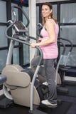 Pregnant woman on crosstrainer Stock Photos