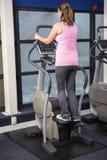 Pregnant woman on crosstrainer Stock Image