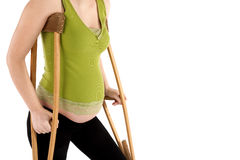 Pregnant Woman with Crutches Royalty Free Stock Photos