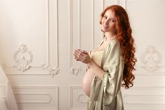 Pregnant woman with cup of tea or coffee Stock Photography