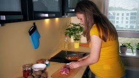 Pregnant woman cut meat with knife on cutting board stock video