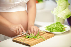 Pregnant woman cuts lettuce on wooden Board Royalty Free Stock Photography