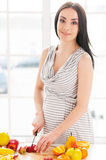 Pregnant woman cutting fruits. Royalty Free Stock Photography