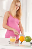 Pregnant woman cutting orange Stock Image