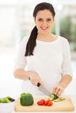 Pregnant woman cutting vegetables Royalty Free Stock Images