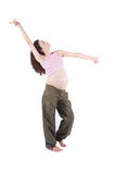 Pregnant woman dancing. Eight month pregnant brunette brown hair woman naked paunch pink shirt green trousers standing and dancing  over white background Stock Photos