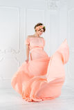 Pregnant woman dancing in pink evening dress flying on wind. Waving fabric, fashion shot. Royalty Free Stock Images
