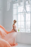 Pregnant woman dancing in pink evening dress flying on wind. Waving fabric, fashion shot. Royalty Free Stock Photography