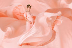 Pregnant woman dancing in pink evening dress flying on wind. Waving fabric, fashion shot. Pregnant woman dancing in pink evening dress flying on wind. Waving Royalty Free Stock Photos