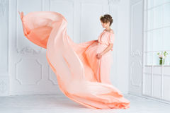 Pregnant woman dancing in pink evening dress flying on wind. Waving fabric, fashion shot. Stock Photos