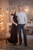 Pregnant woman dating new year. Young beautiful couple posing near the Christmas tree Royalty Free Stock Image