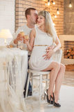 Pregnant woman dating new year. Young beautiful couple posing near the Christmas tree Stock Photos