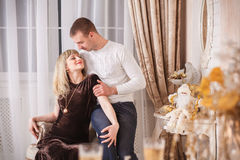Pregnant woman dating new year. Young beautiful couple posing near the Christmas tree Stock Photography