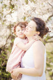 Pregnant woman with daughter in park hugging kissing Royalty Free Stock Photos