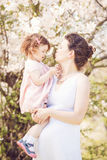 Pregnant woman with daughter in park hugging kissing Royalty Free Stock Photo