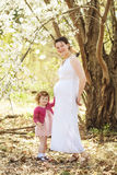 Pregnant woman with daughter in park royalty free stock photography