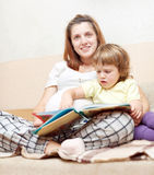 Pregnant woman and daughter reads  book Stock Photo