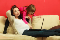 Pregnant woman and daughter sitting with laptop Stock Photo