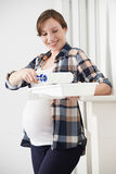 Pregnant Woman Decorating Nursery At Home Stock Image