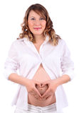 Pregnant woman depicts heart by hands on belly Royalty Free Stock Photography