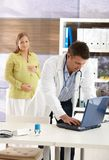 Pregnant woman at doctor. Pregnant woman standing in consulting room, smiling, doctor typing on computer Stock Photos