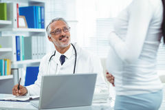 Pregnant woman with doctor at clinic Royalty Free Stock Photos