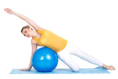 A pregnant woman does gymnastics with ball. The young pregnant woman, the blonde with brown eyes, is dressed in a yellow jersey and white sports pants, carries Royalty Free Stock Photos
