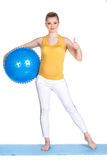 A pregnant woman does gymnastics with ball. The young pregnant woman, the blonde with brown eyes, is dressed in a yellow jersey and white sports pants, carries Royalty Free Stock Image