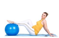 A pregnant woman does gymnastics with ball Stock Photos