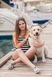 A pregnant woman with a dog on the dock. Stock Photography