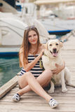 A pregnant woman with a dog on the dock. Stock Photos