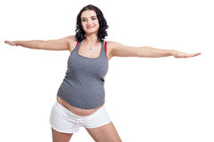 Pregnant woman doing aerobics exercises. Standing on a gym mat with her arms extended improving her breathing and cardiovascular system ahead of the birth Royalty Free Stock Photos