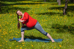 Pregnant woman doing asana Utthita parsvakonasana outdoors Royalty Free Stock Photos