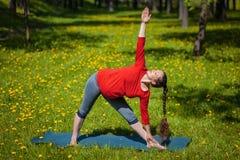 Pregnant woman doing asana Utthita trikonasana outdoors Royalty Free Stock Image