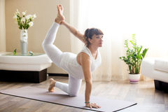 Pregnant woman doing Bird-Dog yoga pose at home Royalty Free Stock Image