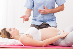 Pregnant woman doing breathing exercise Stock Photos