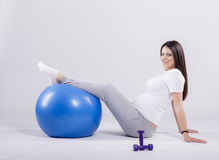 Pregnant woman doing exercise Stock Images