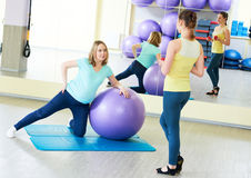 Pregnant woman doing fitness ball exercise with coach. Young pregnant women doing fitness ball exercise with female instructor coach in sport club Royalty Free Stock Photo