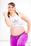 Pregnant woman doing fitness exercises. Smiling beautiful pregnant woman doing fitness exercises at living room Royalty Free Stock Image