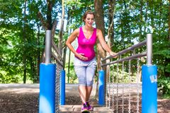Pregnant woman doing fitness sport in climbing park Stock Image