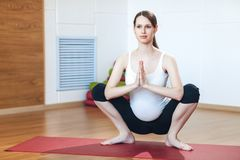Pregnant woman doing gymnastic exercises. Practicing yoga royalty free stock photography