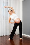 Pregnant woman doing gymnastic at home Royalty Free Stock Photography