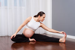 Pregnant woman doing gymnastic at home Royalty Free Stock Images