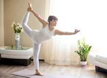 Pregnant woman doing Lord of the Dance yoga pose at home Royalty Free Stock Photography