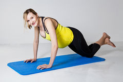 Pregnant woman doing push-up exercise Stock Images