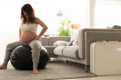 Pregnant woman doing relax exercises with a fitball. Pregnant woman doing relax exercises with a fitness pilates ball at home Royalty Free Stock Images